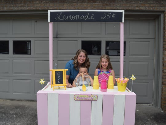 Stephanie, Grey and Hadley Ranes pose next to the lemonade