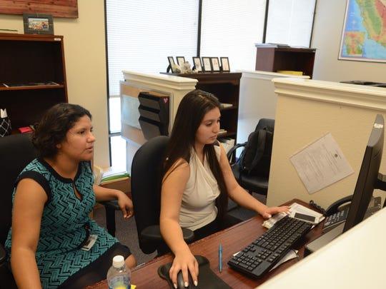 Desert Mirage High School students Michelle Chavez, left, and Alejandra Sanchez, right, work on a project at Assemblymember Eduardo Garcia's Coachella office.