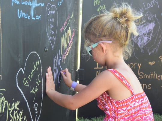 Lily Hart, 5, writes a message to her great grandparents
