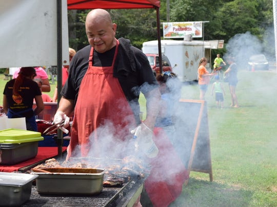 Bob Balan of Famous Sgt. Bob's Smoked BBQ & Grill tends the grill during Christmas in July at Parvin State Park. This year the event included food trucks. Photo/Jodi Streahle