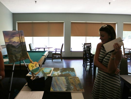 Danielle Girten views paintings at one of the vendors