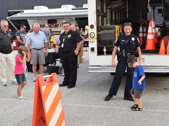 Officer Cassandra Kudzinowski (right), of the York Area Regional Police Department, watches as children try to complete field sobriety tests while wearing beer goggles during the department's National Night Out event in Dallastown, Tuesday, Aug. 1. Jason Addy photo.