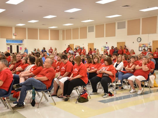 More than 300 people, many wearing red T-shirts to
