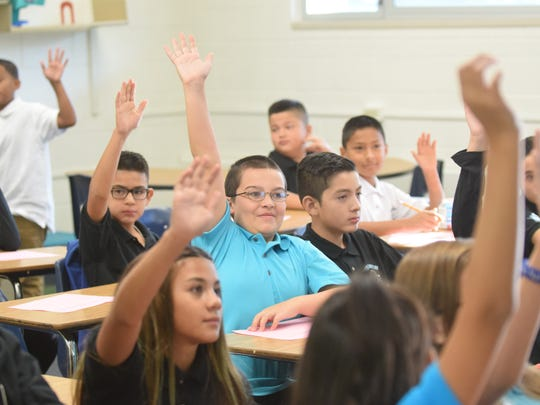 Children raise their hands in a Dilworth Middle School classroom on Aug. 7, the first day of school.