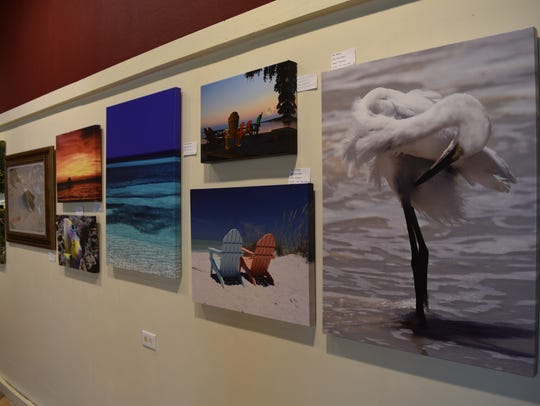 Photographs for sale hang on the back wall of the gallery.