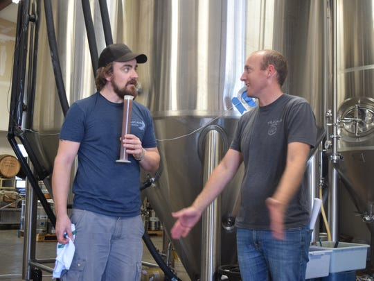 Andy Crocker, left, and Jeff Hansen, the co-founder and brewmaster at Wildcard Brewing, compare notes while working on a collaboration with Woody's.