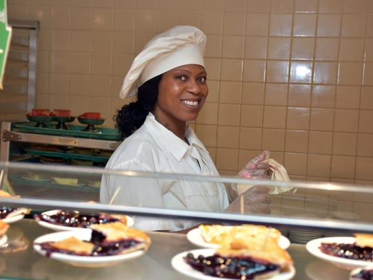 S&S Cafeteria employee Katie Rushin adds a finishing touch to the freshly made pies available for dessert in a 2017 file photo.