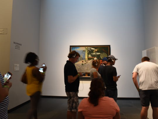 Museum goers listen to an audio tour as they look at art and sculptures by Salvador Dali at The Dali Museum in St. Petersburg.