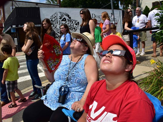 Samantha Lopez, right and  Saudhi Lopez sit on the corner of Main Street near the library looking at the solar eclipse with glasses as they wait to view it through the telescopes set up.