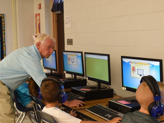 Granville Thompson guides second-graders through a computer program inside his classroom at Pelican Marsh Elementary School on Aug. 22, 2017. Thompson has taught for nearly 50 years.