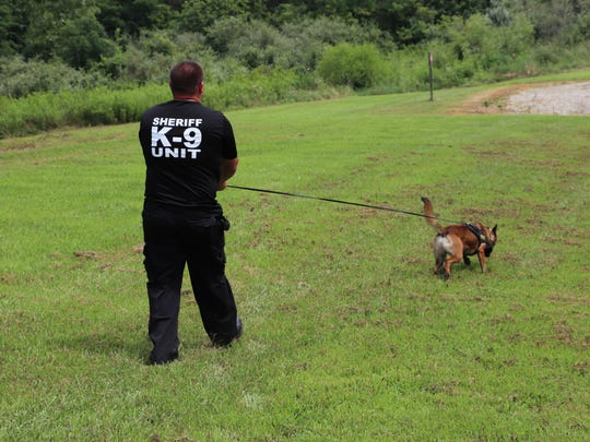 Deputy Steve Mox of the Coshocton County Sheriff's Office takes Chili out during a training exercise. The pair were matched as a K-9 unit in April and have been patrolling about a month.