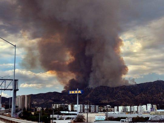 Heavy black smoke rises as a wildfire burns dozens
