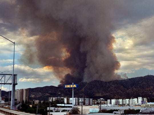Heavy black smoke rises as a wildfire burns dozens