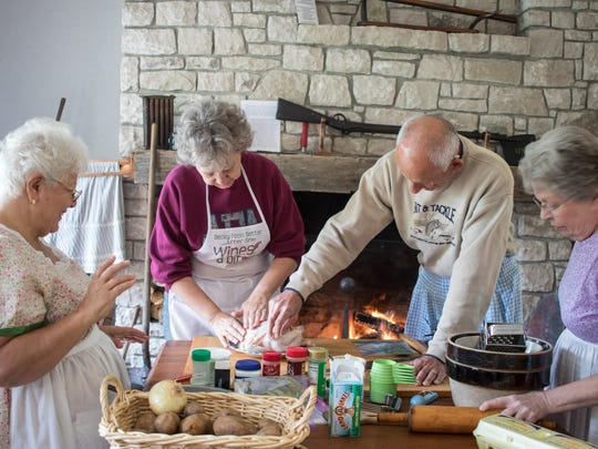 Linda and John Hartigan prepare the chicken for roasting under the watchful eyes of Georgette Machar,  left, and Becky Shemenski, right.