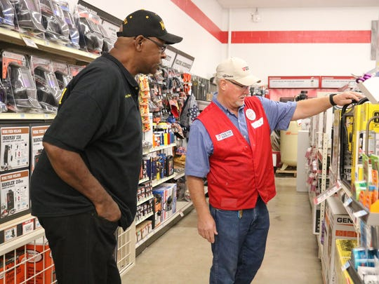 Magistrate Chuck Voss (right) assists Bobby Ray (left) during the grand opening of Tractor Supply.