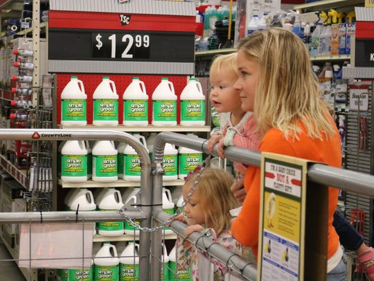 Dr. Kate Baker and her two daughters take a peek at the baby chicks at Tractor Supply.