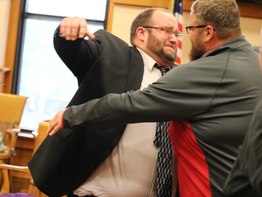Sloopy's owner Brad Corbin, left, hugs his brother,
