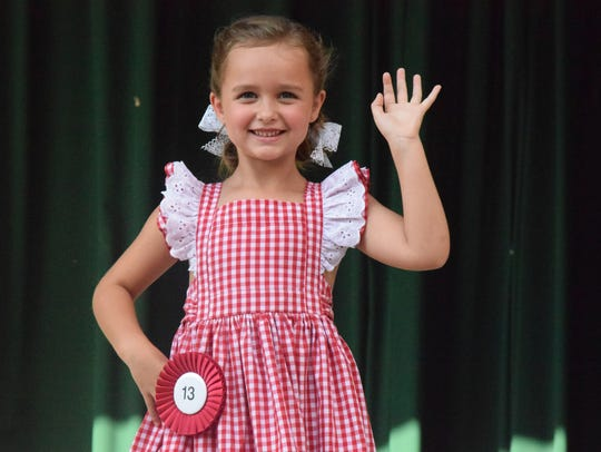 A contestant smiles and waves during the Corn Festival Little Mister and Miss pageant held in 2017