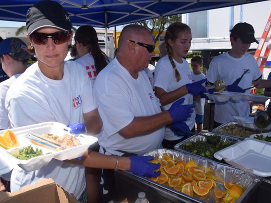 Volunteers fill trays with meals cooked by professional