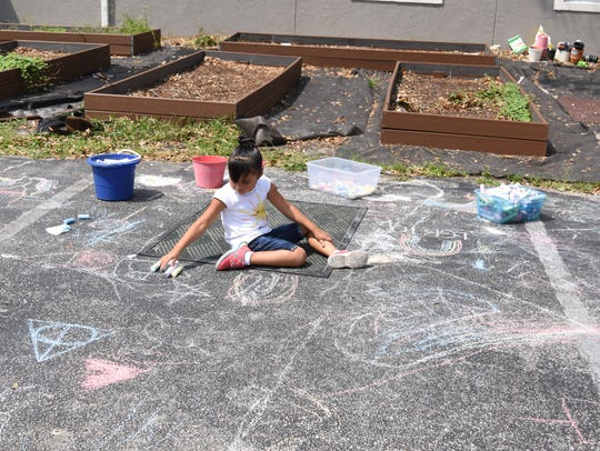Children draw chalk art at Grace Place For Children