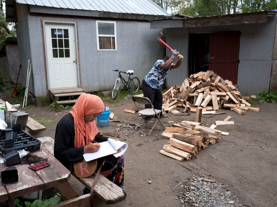 In this Sept. 7, 2017 photo, a girl studies for school while a man chops wood in the Muslim enclave of Islamberg in Tompkins, N.Y.