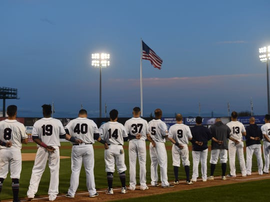 Member of the Somerset Patriots baseball team stand during the national anthem.