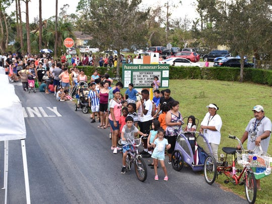 People wait in line at a mobile pantry at Parkside elementary in Naples.