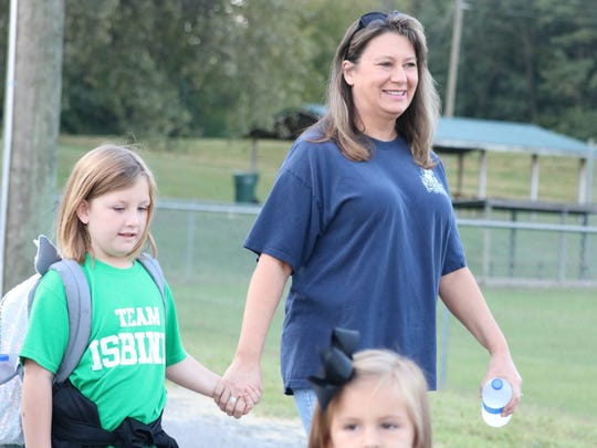 Chloe Mayes walks with her mom to the elementary school.