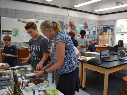 Science teacher works with Maclay students on a project on river ecology.