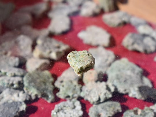 Trinitite, glassy residue left on the desert floor following the Trinity test, sits on display for visitors to view Saturday.