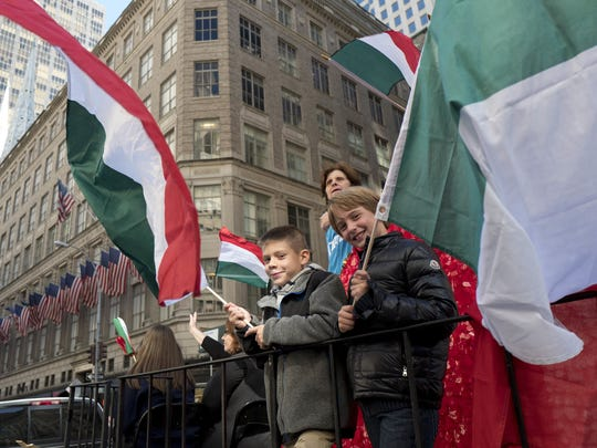 Boys wave Italian flags on Oct. 10, 2016, while riding a float in the Columbus Day Parade in New York.