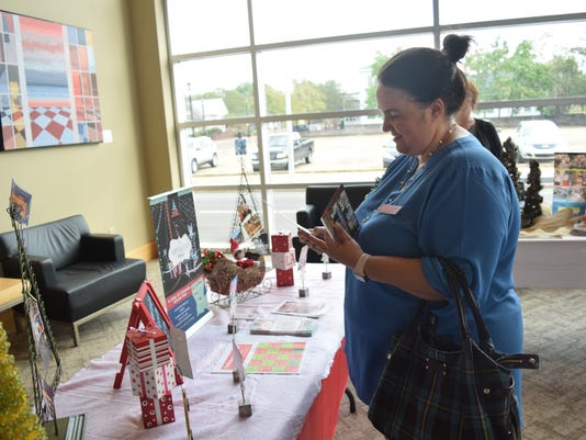Shanna Hartman, Children's T.R.E.E. House operations manager, looks over brochures at the news conference held Tuesday at the Coughlin-Sauncers Performing Arts Center for the Louisiana Holiday Trail of Lights. The trail includes Christmas holiday-related