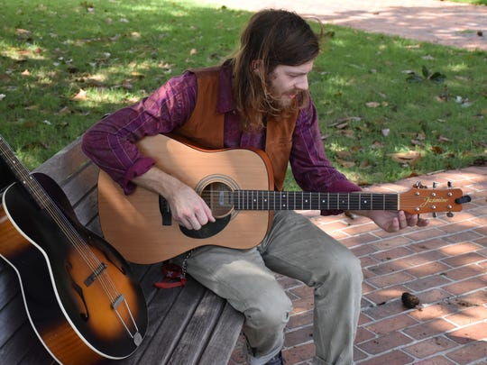 Local musician Joshua Tyrone plays his guitar on Monday, Oct. 9, at Lee Square.