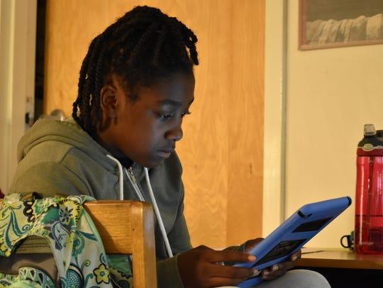 Angelica Martin, 11, works through a math problem on
