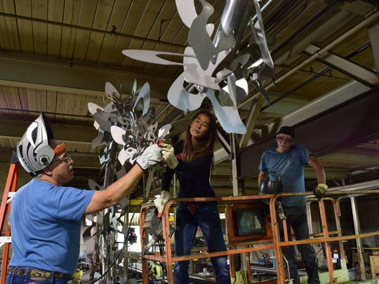 Welders Johnny Ronk and Jimmy Price work with artist Yuri Tsuzuki, center, on her scuplture for the Cancer Survivors Park.