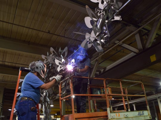 Welders Johnny Ronk and Jimmy Price work on the artwork that will be placed at the Cancer Survivors Park