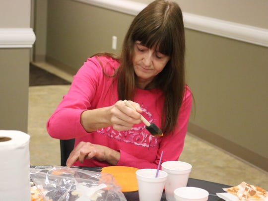 Linda Richardson dips her paintbrush in the paint to