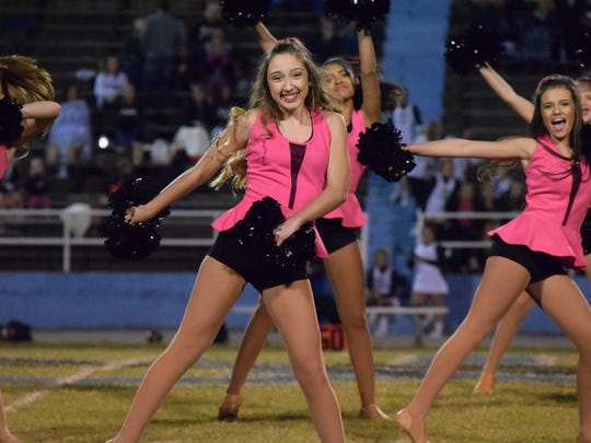 Katelyn Hendrickson smiles as she strikes a pose during the half time preformance.