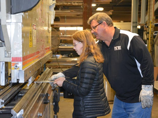 Aubrey Peot, a sophomore at Gibraltar High School, prepares to bend a piece of steel while John Wilz, Hi Tec Fabrication operations manager, supervises during the manufacturing days tour for students at the Sturgeon Bay Industrial Park Friday, Oct. 20, 2017.