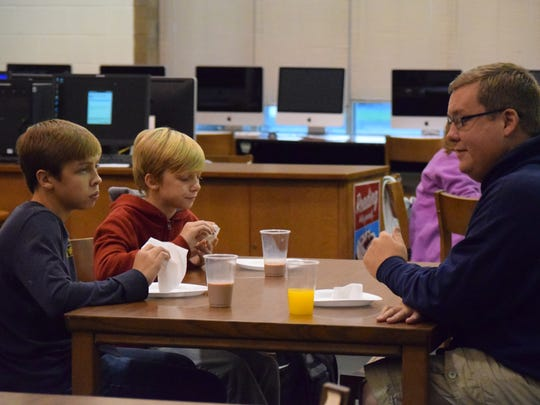 Brock, Riley, and ? Cullen enjoy the donuts served