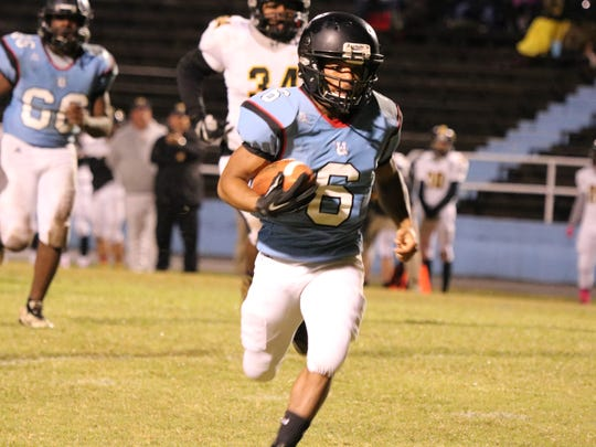 Renato Savage runs the ball for the Braves during Friday night's game.