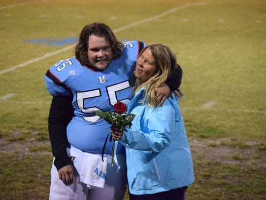 Gage Clements gives his mother Brandy a hug during the ceremony.