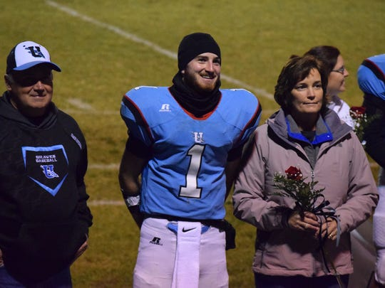 Trey Hutchison smiles during the ceremony, with his mother and father at his side.
