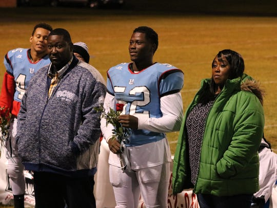 Ross Hicks stands with his mother and father.