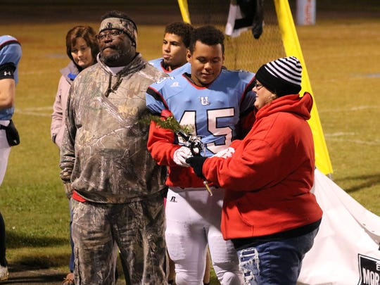 Senior Chance Hill gives his mother a rose during the