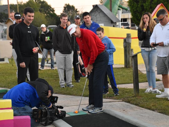 Bubba Watson watches as Jerry Pate lines up a putt at the first mini golf tournament featuring the two pro golf stars at the First Tee of Northwest Florida Goofy Golf Center. You can try to beat Bubba this Sunday.