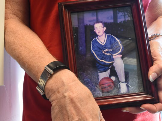 Shelly Church holds a photo of her son Kyle, who died