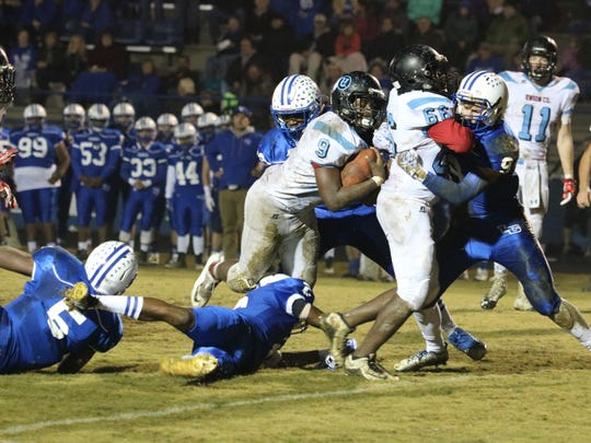 Chris Bledsoe tries to make his way past the opponents, as the Braves hold the tackle.