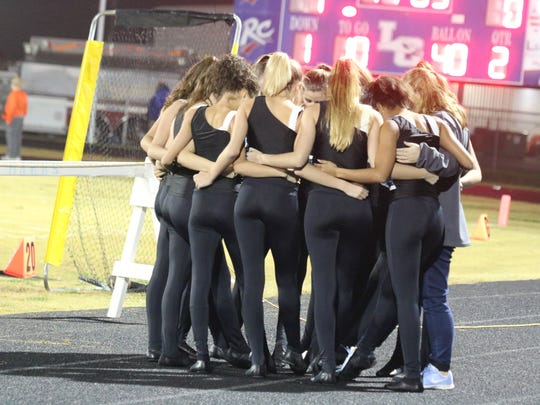 The dancing Bravettes say a prayer before their half time performance.