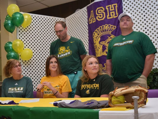ASH softball players Caroline Manzer (center, front) and Briahna Bennett (right, front) sign with Southeastern Louisiana Wednesday. With Caroline are her parents Cindi (left, front) and Craig Manzer and with Briahna is her father Shane Bennett.